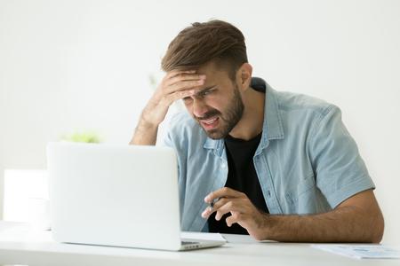 Giovane confuso frustrato dal problema online che esamina lo schermo del computer portatile, lavoratore preoccupato che fa duro lavoro sul computer che fa le note, lo studente si sente stressato sull'apprendimento difficile che fallisce prova o esame