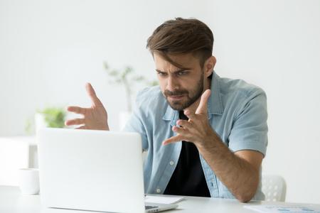 Empresario enojado frustrado indignado por un problema de computadora portátil, hombre loco furioso que usa la computadora mirando la pantalla furiosa después del error de bloqueo del software de la PC, el tipo molesto frustrado no está de acuerdo con las noticias falsas en línea