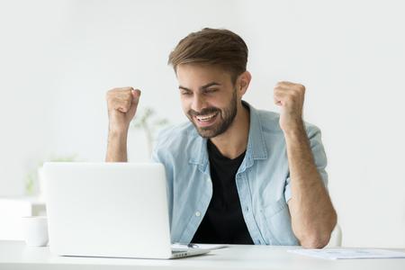 Heureux homme excité célébrant le résultat de la réussite de la victoire en ligne en regardant un écran d'ordinateur portable, entrepreneur prospère excité par de bonnes nouvelles par e-mail, motivé par une victoire commerciale ou une nouvelle opportunité d'emploi