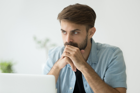 Thoughtful serious young man lost in thoughts in front of laptop, focused businessman or absent-minded student thinking of problem solution, worried puzzled manager pondering question at work