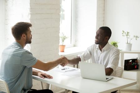 Uomini d'affari africani e caucasici che si stringono la mano sulla scrivania, partner bianco soddisfatto che chiude un affare di successo con un investitore nero, stretta di mano dopo aver raggiunto un accordo o essere assunto Archivio Fotografico - 95287857