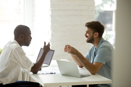 Diverse friendly multiracial colleagues discussing new interesting idea talking at workplace, african american and caucasian businessmen laughing having fun pleasant conversation at work in office Stock Photo