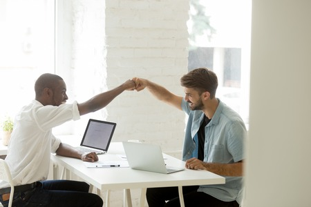 Smiling diverse businessmen giving fist bump celebrating common goal achievement or shared business success, successful teamwork, motivated african and caucasian colleagues happy by good work result