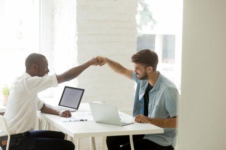 Sourire d'hommes d'affaires diversifiés donnant le coup de poing célébrant la réalisation d'un objectif commun ou la réussite commerciale partagée, un travail d'équipe réussi, des collègues africains et caucasiens motivés heureux par un bon résultat de travail