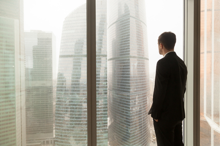 Mann im Anzug, der mit den Händen in den Hosentaschen schauen durch Fenster auf Stadtlandschaft mit Wolkenkratzern steht. Geschäftsmann, der an Perspektiven denkt und vom Unternehmenserfolg träumt. Rückansicht