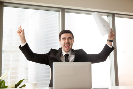 Excited businessman waving business papers in hands and screaming loudly with joy at desk in office. Happy boss celebrating with vivacity company success. CEO enjoying growth of Financial indicators Stock Photo