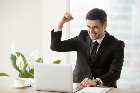 Happy smiling businessman celebrating victory in business, excited with good results in work, feeling satisfaction because of making great deal while sitting at work desk and looking on laptop screen