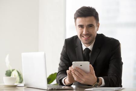 Porträt des hübschen Geschäftsmannes sitzend am Schreibtisch vor Laptop, unter Verwendung der digitalen Tablette und Kamera mit glücklichem Lächeln betrachtend. Finanzdirektor der Firma, der online mit Geschäftspartnern kommuniziert