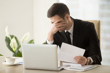 Businessman shocked with bad news in letter, upset because of loan refusal, feeling suppressed when receiving notification about company bankruptcy or debts to bank. Depression through work dismissal