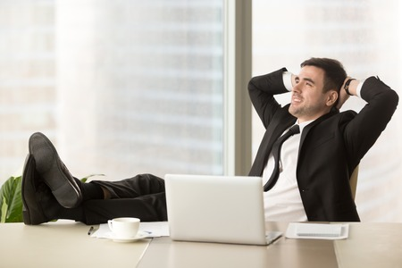 Relaxed businessman feeling positive when resting in office with hands behind head and legs on desk. Company leader enjoying success, dreaming of achievements in business. Clerk taking break in work