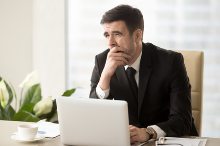 Tired businessman covering his mouth with hand when yawning at desk in office. Office worker feeling lack of sleep during work day, suffering of fatigue or overwork, languishing through boring work Stock Photo