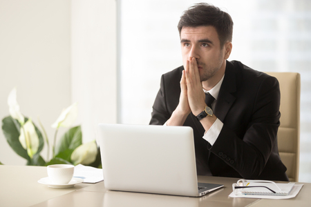 Worried company leader thinking about problem solution, pondering important question, frustrated because of difficulties in business while sitting at desk. Religious businessman praying at workplace