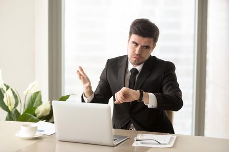 Homme d'affaires stressé en regardant la montre-bracelet et inquiétant par manque de temps, en retard sur la réunion d'affaires, échec du délai. Employé de bureau fatigué et frustré nerveux après une trop longue journée de travail Banque d'images