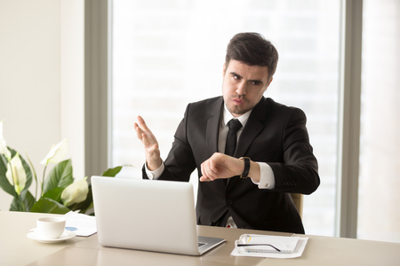 Stressed businessman looking at wrist watch and worrying because of lack of time, late on business meeting, failing deadline. Tired and frustrated office worker nervous after too long day at work