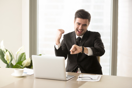 Excited businessman yelling with joy when sitting at desk in front of laptop and looking at wrist watch. Happy office worker finishing work before deadline, glad because of ending of working day