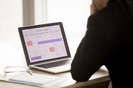 Indietro sopra la vista della spalla dell'uomo d'affari che si siede allo scrittorio davanti al computer portatile con programma di lavoro sullo schermo. Responsabile dell'azienda che utilizza le app di calendario e pianifica le attività lavorative e le priorità negli affari per il prossimo mese