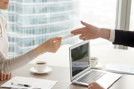 Businessman stretching out hand with blank business card over desk with laptop, coffee cups and documents to satisfied businesswoman after successful contract negotiation in company office. Close up