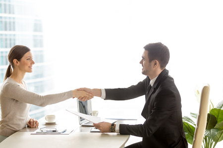 Male human resources manager holding resume and welcoming with handshake female job candidate in company office. Business partners agreeing with terms of contract. Successful negotiation. Side view