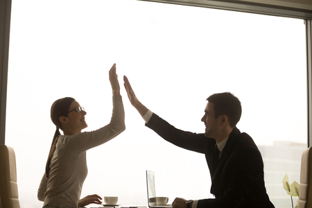 Happy smiling female and male business partners giving high five while sitting at desk in office. Businesswoman congratulating businessman with concluding good deal. Company employees enjoying success Stockfoto - 95954136