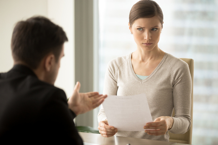 Millennial businesswoman with skeptical facial expression holding contract document and listening unconvincing offer of business partner. Suspicious terms of agreement, doubtful investor, fraud, scam