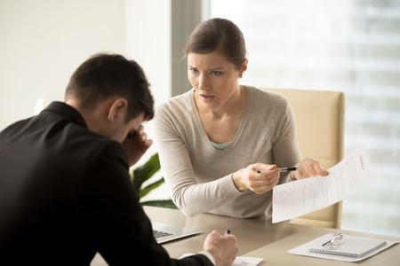 Unbefriedigter verärgerter weiblicher Kunde, der auf Vertragsbedingungen zeigt, während die Befriedigung von Ansprüchen von frustriertem Firmenmanager verlangt wird. Ermüdet von dem unproduktiven Verhandlungsgeschäftsmann, der auf Partner hört Standard-Bild