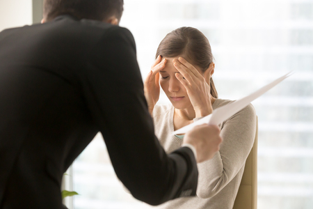 Stressed millennial woman listening claims of angry boss on mistakes in report. Frightened by prospect of dismissal female office worker worried because of serious fail in work. Scandalous, mad client Banque d'images
