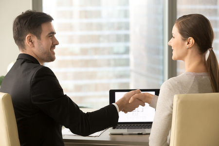Satisfied with results of business meeting businessman and businesswoman shaking hands while sitting at desk in front of laptop. Male real estate agent congratulating female client with buying home