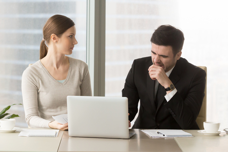 Tired businessman yawning when sitting at desk with female colleague during meeting in office, businesswoman looking with confusion on bored male coworker. Lack of sleep and narcolepsy, bad manners Stock Photo