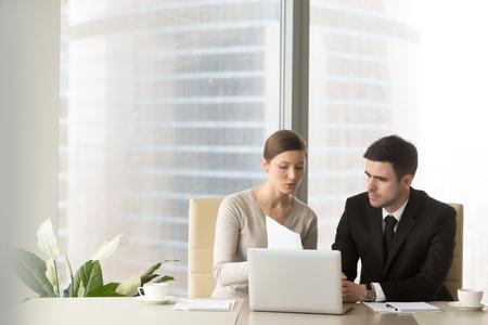 Empresaria milenaria que discute los indicadores de la compañía con el socio comercial masculino en la reunión en la oficina. Consultor financiero femenino, experto en crédito que explica los términos del contrato al cliente o inversionista