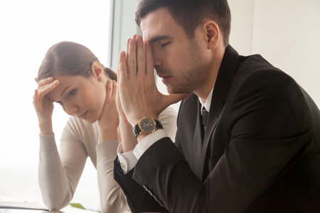 Stressed male and female business persons sitting at desk, hard thinking about problem. Businessman and businesswoman shocked, bad news, company bankruptcy, mistake in work, big reduction in office Standard-Bild