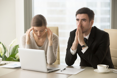 Tired stressed businessman and businesswoman sitting at desk and pondering over problem. Difficult negotiations between business partners, lack of understanding among colleagues, difficulties in work Foto de archivo