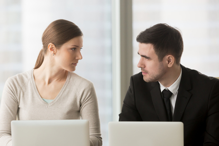 Female and male colleagues carefully looking on each other when sitting at desk. Competition in work, professional rivalry and jealousy. Feminism, equal gender rights and opportunities in business