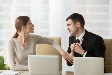 Man with deliberately sad facial expression asking female coworker to help with difficult project to leave work earlier, inviting colleague to date. Businesswoman refuses in request of foolish admirer