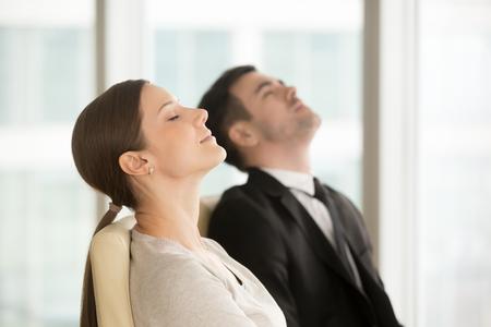 Erfüllte entspannte stillstehende Geschäftsfrau und Geschäftsmann beim Sitzen auf Stühlen mit geschlossenen Augen, kurze Pause für nachdenkliche Praxis während des Tages im Büro machend. Büroangestellte, die Erfolg sich vorstellen Standard-Bild