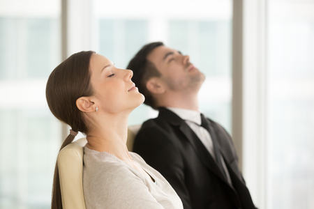 Satisfied relaxed businesswoman and businessman resting while sitting on chairs with closed eyes, taking short break for meditative practice during day in office. Office workers imagining success