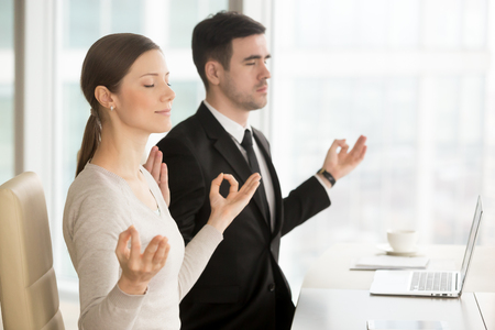 Female and male coworkers meditating at workplace in office. Businesswoman and businessman practicing eastern spiritual practices before starting work to get clear and calm mind, short relaxing break