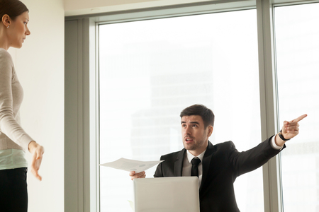Angry CEO with report in hand pointing on door, asking to leave responsible for financial mistakes female office worker, guilty woman looking on boss with confusion. Firing because of bad work results