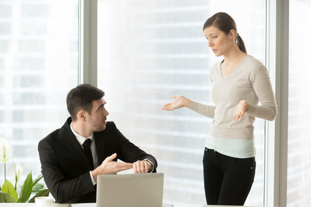 Company leader pointing on wrist watch when asking female employee about delay in project, fail deadline, deviation from schedule, late for work. Woman making excuses because of absence from work