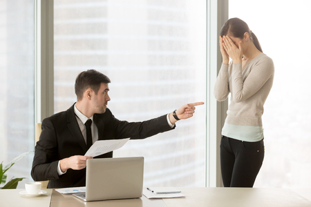 Serious male executive manager with bad financial report in hand blaming inexperienced female employee in mistakes at documents, stressed and upset young woman cowering her face with hands and crying Stock Photo