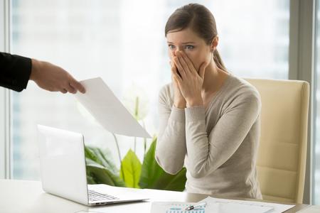 Junge Frau schockiert, als sie Entlassungsmitteilung vom Chef erhielt. Umgekippte Arbeitnehmerin, die wegen der Fehler in den Berechnungen sich sorgt. Büroangestellter kann nicht daran glauben, einen Arbeitsvertrag zu brechen