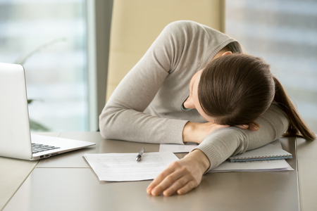 Tired female office worker lying on desk with laptop and business documents because of overwork. Exhausted from hard paperwork businesswoman sleeping on workplace, taking short napping during work day