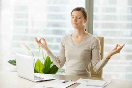 Relaxed woman meditating at workplace, practicing eastern spiritual practices for stress relief and mental health while sitting at desk in front of laptop. Short break in work for strength recovery 免版税图像