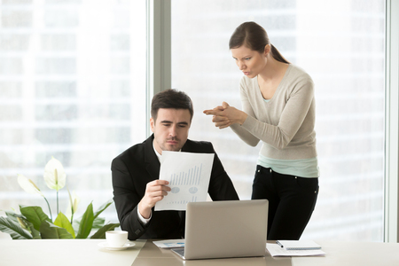 Angry woman aiming with finer gun at head of her hateful boss who attentively reading financial report at desk. Intrigues of office colleagues, bad coworkers relations, hidden negative among employees Stock Photo