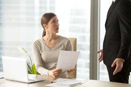 Confused young female employee listening claims of head manager on mistakes in business papers, surprised by complaints from boss. Woman shocked when getting notification about dismissal at work Stockfoto