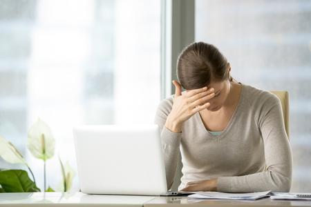 Betonter und müder weiblicher Angestellter, der unter Kopfschmerzen beim Sitzen am Schreibtisch vor Laptop leidet. Frustrierte nervöse Geschäftsfrau, die mit Spannung während des Arbeitstages kämpft und stark an Problem denkt