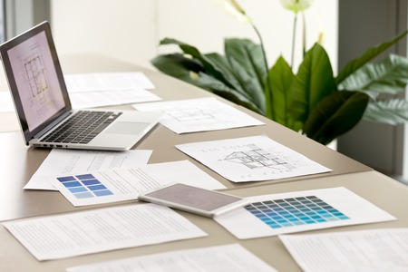 Close up photo of woman hand pointing on blue color sample on pantone swatch lying on desk with documents and digital tablet with house architectural plans on screen. Interior designers team at work