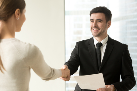 Smiling male manager with contract document in hand handshaking with female client or business partner in company office. Happy businessman welcoming businesswoman before negotiations