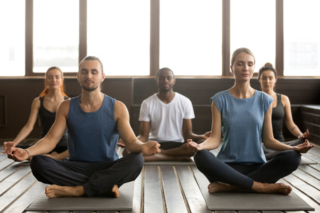 Group of young sporty afro american and caucasian people practicing yoga lesson, sitting in Sukhasana exercise, Easy Seat pose with mudra gesture, working out, students training in sport club, studio