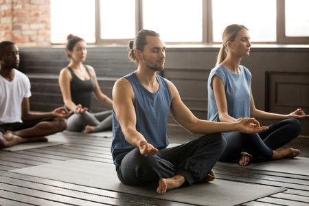 Group of young sporty people practicing yoga lesson, sitting in Sukhasana exercise, Easy Seat pose with mudra gesture, students working out in club, indoor, studio Stock Photo