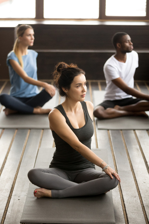 Group of three young sporty afro american and caucasian people sitting in parivritta sukhasana pose, students working out in club with female instructor, indoor, studio Banco de Imagens